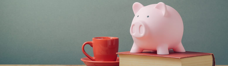 A piggybank resting on a book next to a cup of coffee.