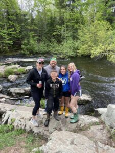 jeanette williams, a BSN graduate with her family by a river