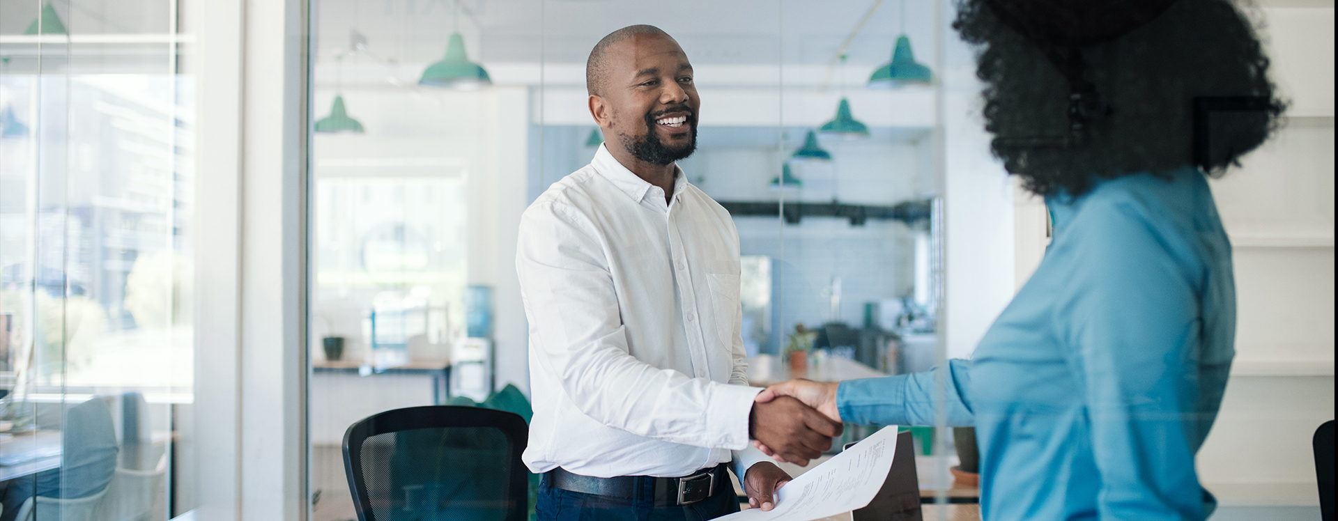 Two professionals shaking hands in a sunlight workspace