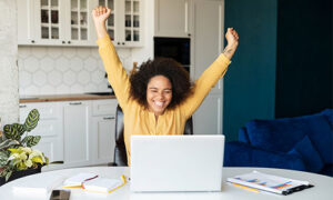Woman celebrating in front of laptop computer